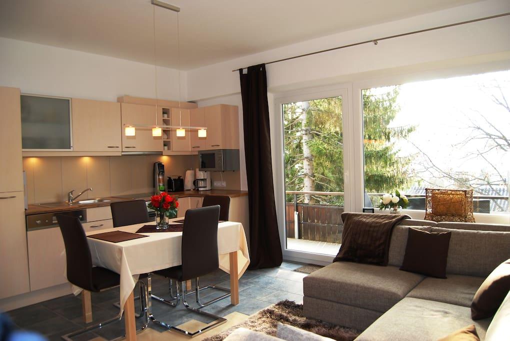 Wohnzimmer mit Küche und Essbereich und wunderschönem Ausblick auf die Alpen