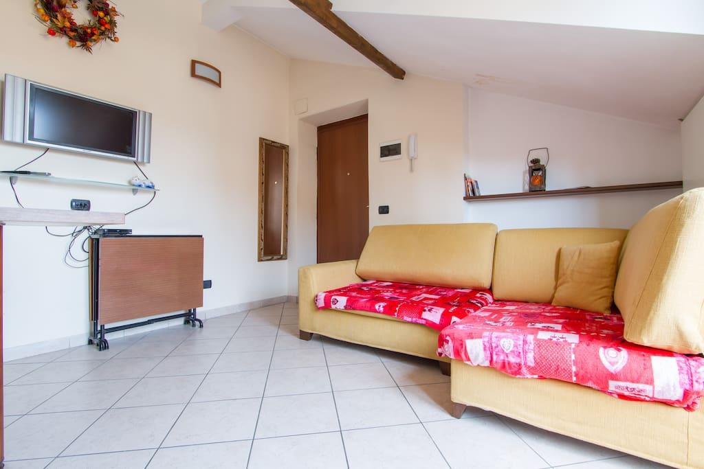 divano a penisola,  tavolo richiudibile e televisore alla parete
