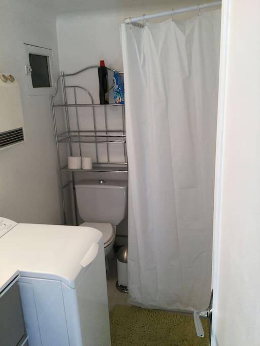 Salle de bain avec une douche, un WC, un lave linge et un lavabo