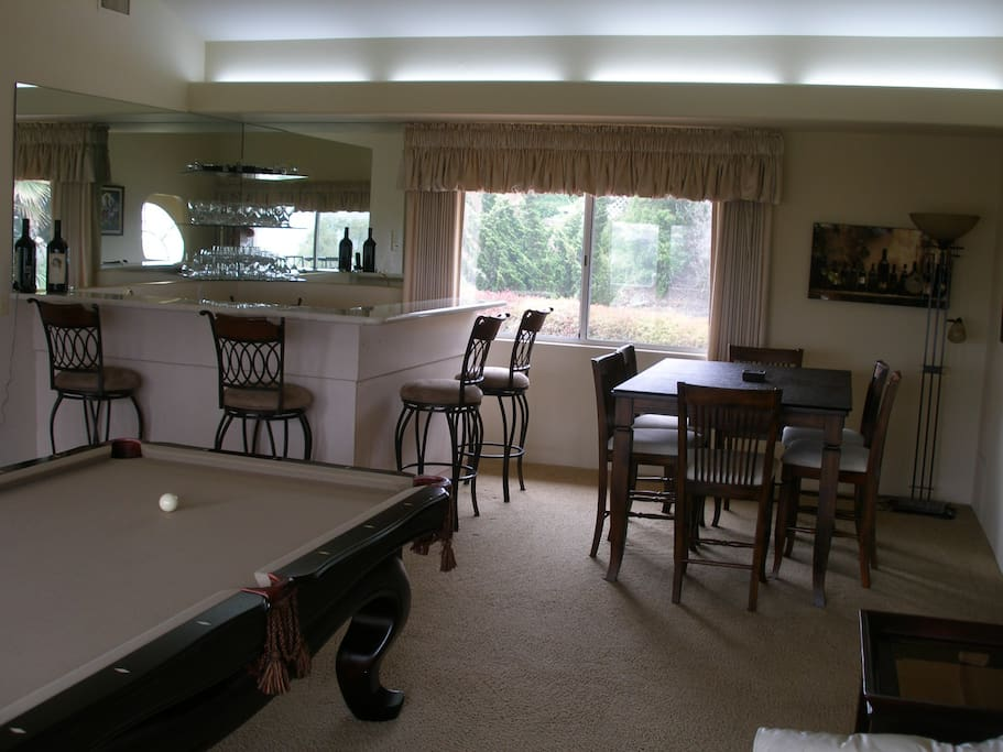 Game room with wet bar balcony with view of golf course and lake