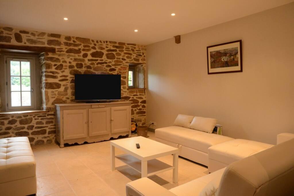 Un salon alliant modernité et traditions avec un mur de pierres de la Rhune