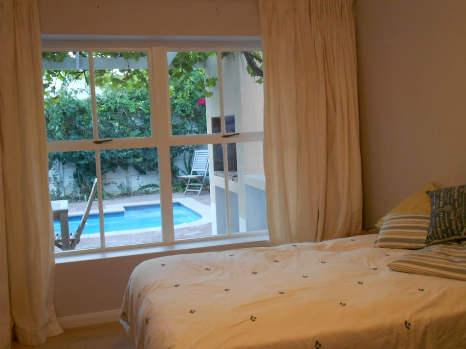 Large double bedroom with en suite bathroom. Lovely view onto garden and pool.