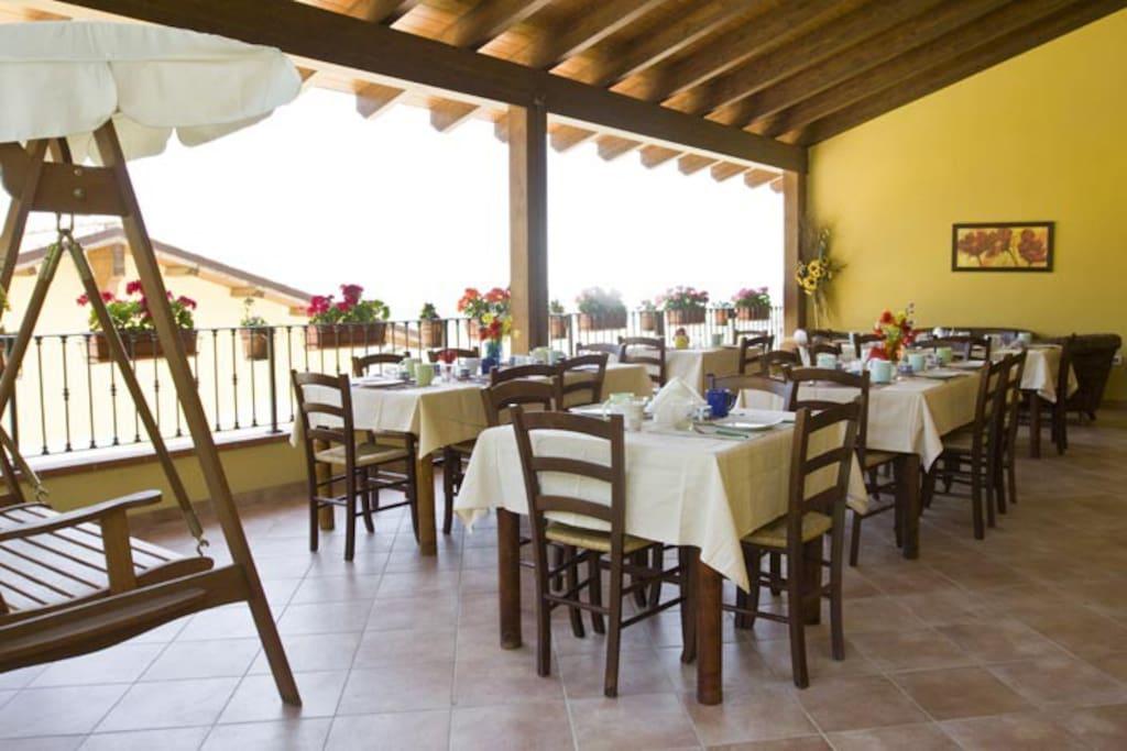 Terrazzo adibito alle colazioni, con tetto in legno ed ampia vista panoramica su mare e montagne.