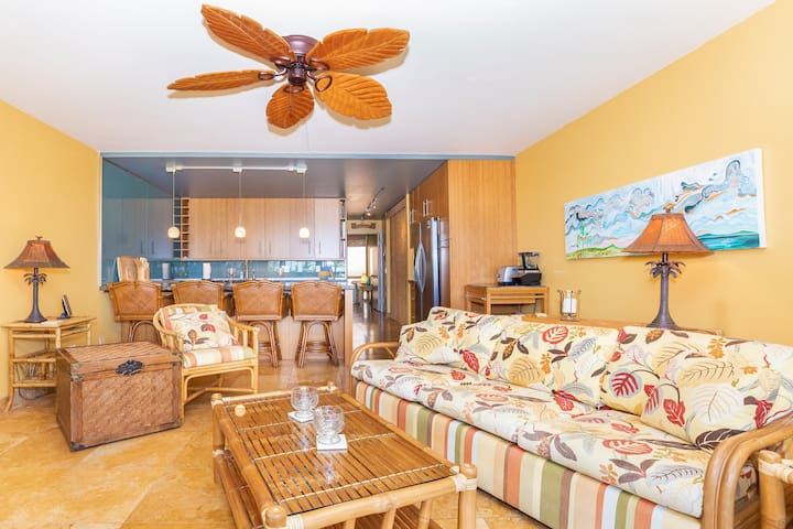Living area features cozy sofabed, comfy chairs, ceiling fan, air conditioner, and tiki-inspired furnishings throughout.  Kitchen area includes bar seating for four.