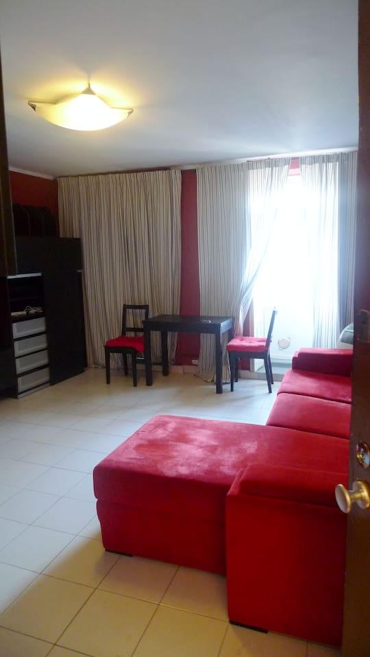 Sala de estar com sofá-cama. Janelas e varanda voltada para o Rio Douro