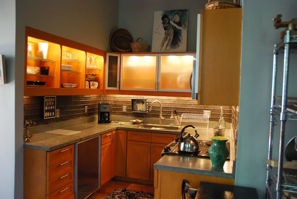 Kitchen with small under counter Subzero refrigerator, concrete counters, double stainless sink.