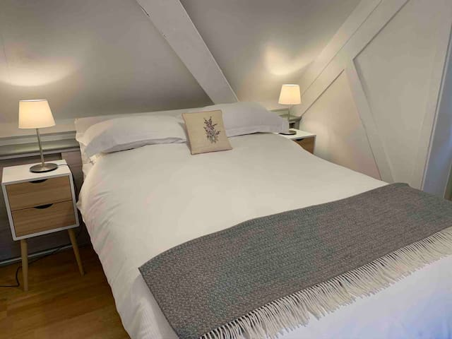 Comfortable and cosy bedroom with queen size bed and a hair drier in the drawer. Plug sockets include USB connections for electronics charging.