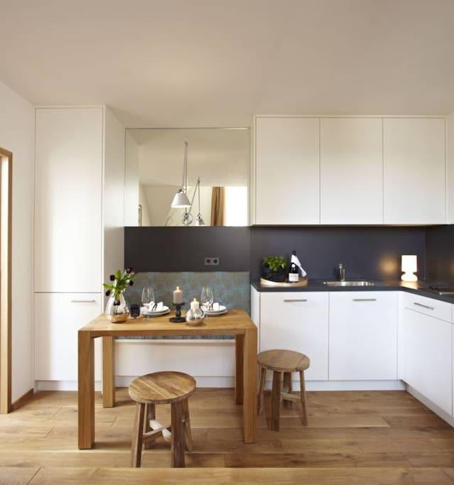 Die coole Küchenzeile mit allem was man braucht: Vor der gemütlichen Sitzbank der massive Eichholztisch.