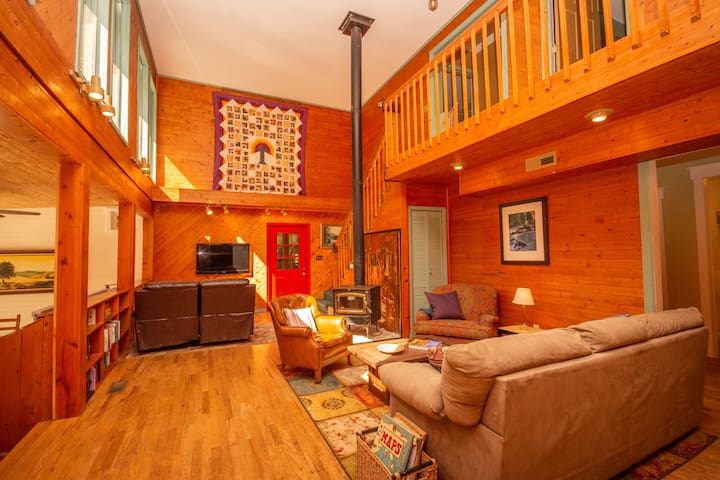 Vaulted main living area with south facing windows, local art, and wood-burning stove.