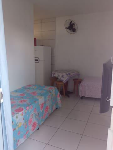 Sala com 2 camas box e solteiro, televisão e mesa com 4 bancos.