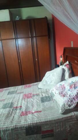 Quarto com cama de casal , q possue uma sacada e ar condicionado.