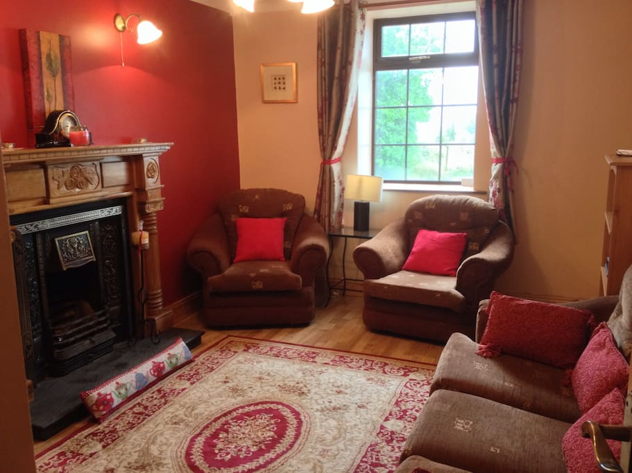 Sitting room with large tv, open fire, and comfy sofas.