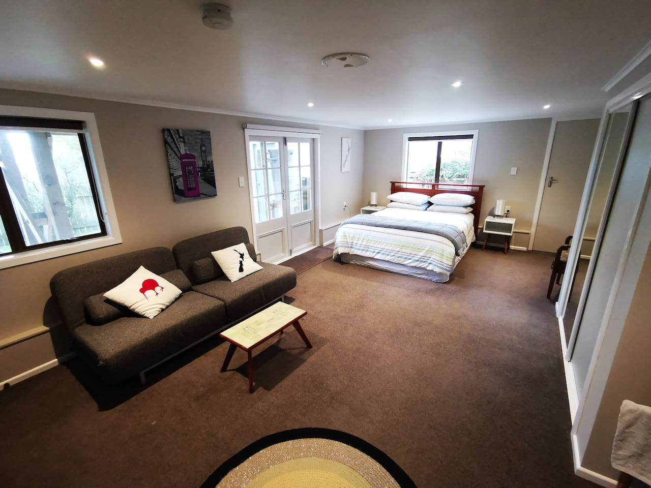 Suite showing Queen bed. Parking is right outside the window behind the bed.
