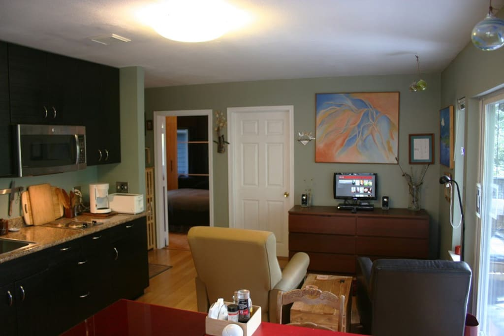 Living room with LCD TV, kitchenette, comfortable sofa seats and dining table.