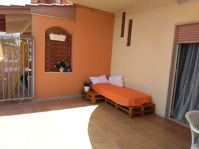 Ampia veranda attrezzata di tavolo, 4 sedie, divanetto e ombrellone