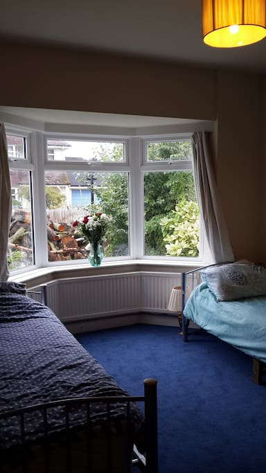Large facing front bay window (with wood awaiting splitting). Twin room with 3rd proper mattress stored under one of the beds