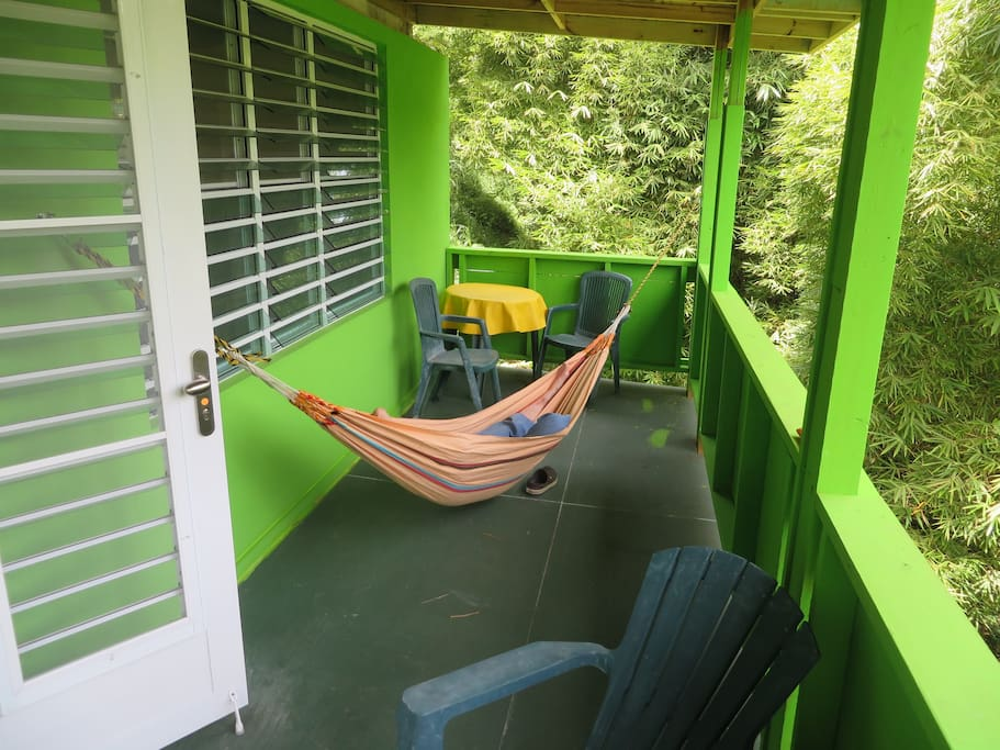 The terrace has two hammocks and outdoor chairs and tables.