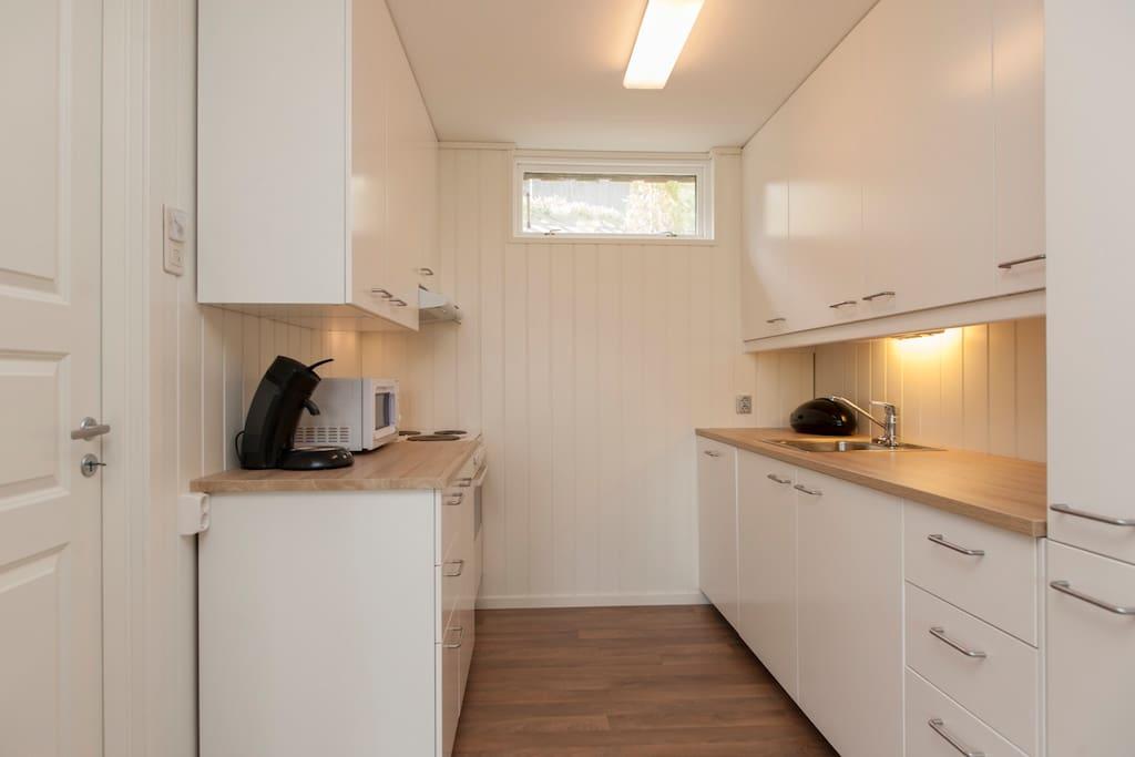 Kjøkken med integrert kjøleskap/fryser og oppvaskmaskin. Alt av kjøkkenutstyr i skuffer og skap. The kitchen is fully equipped, with integrated fridge/freezer and dishwasher.