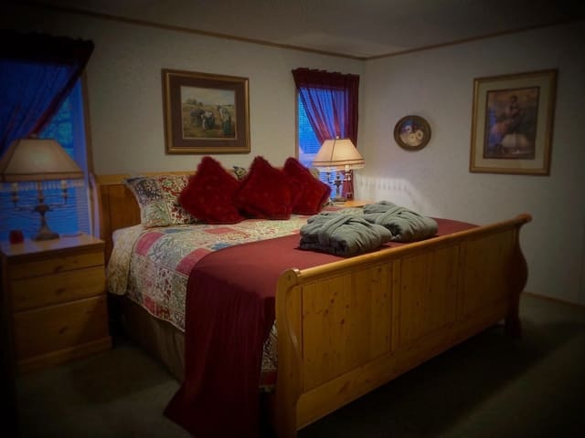 King sleigh bed in master bedroom. Also has a comfy futon chair to curl up in and read a good book, or to convert into a single bed for extra sleeping.