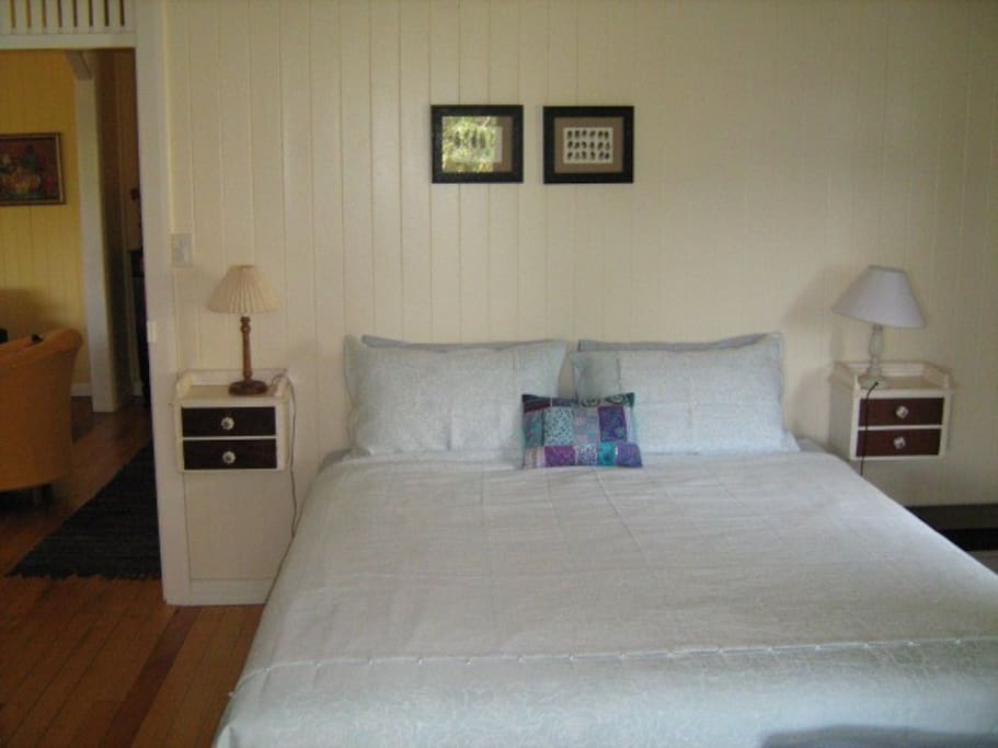 Comfortable king-sized bed in the main bedroom, which  has french doors opening to the deck.