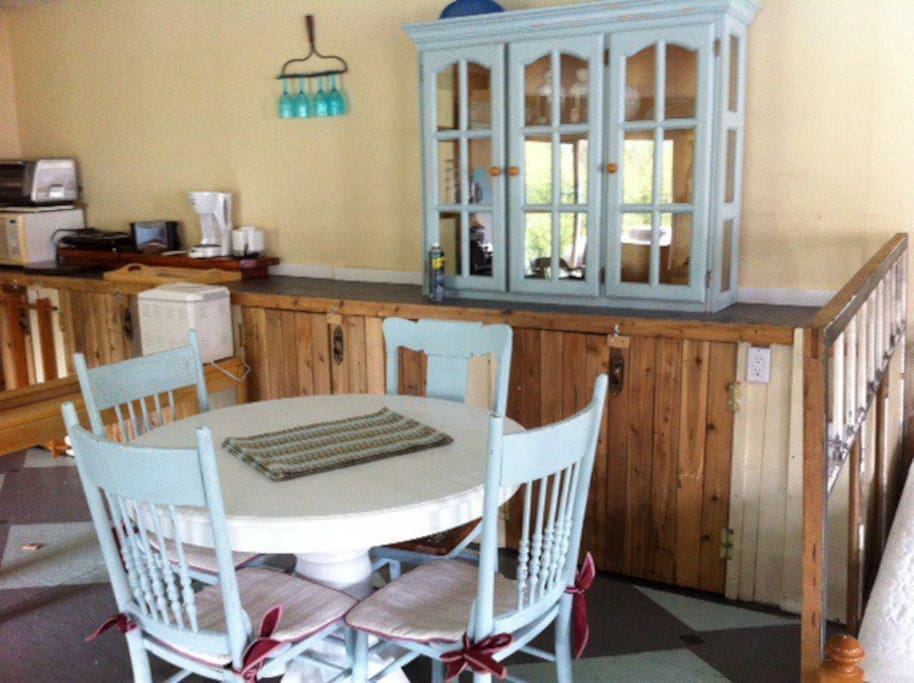 The dining area has table and chairs and all the dishes for your family needs.