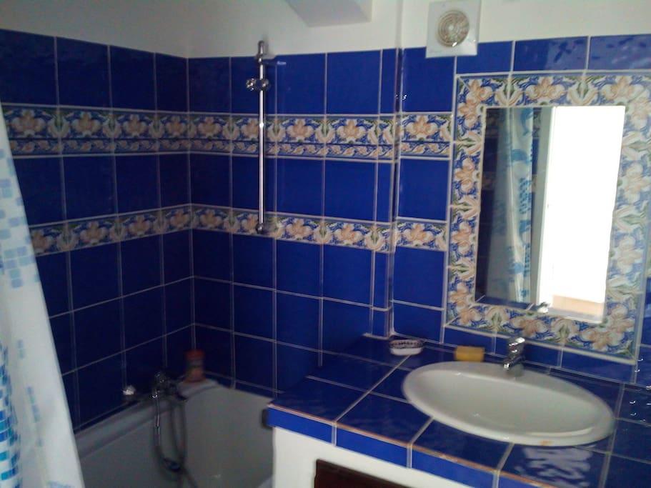 Salle de bain avec baignoire, vasque et   toilette.