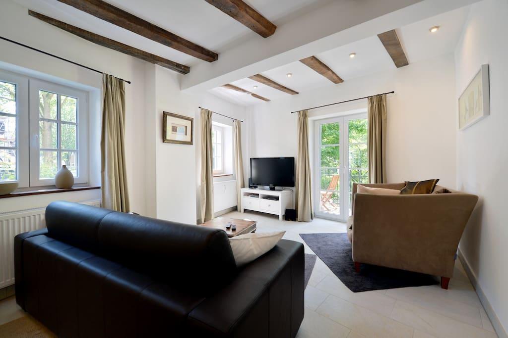 Das Wohnzimmer mit dem Schlafsofa (1,5 x 2,0 m), Zugang zur Terrasse, Sat-TV (deutsch und englisch) und WLAN