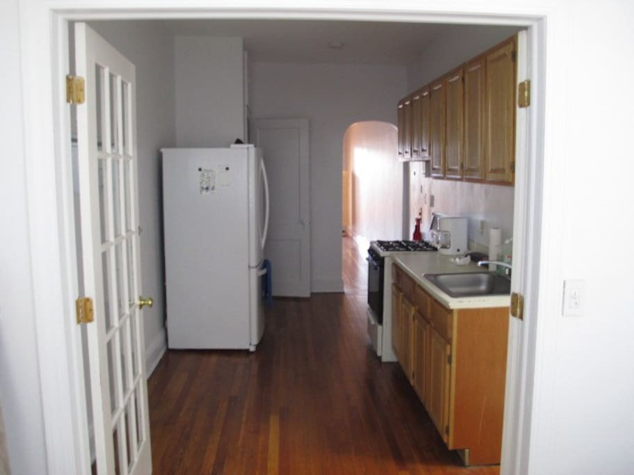 Large kitchen with gas stove and huge fridge.