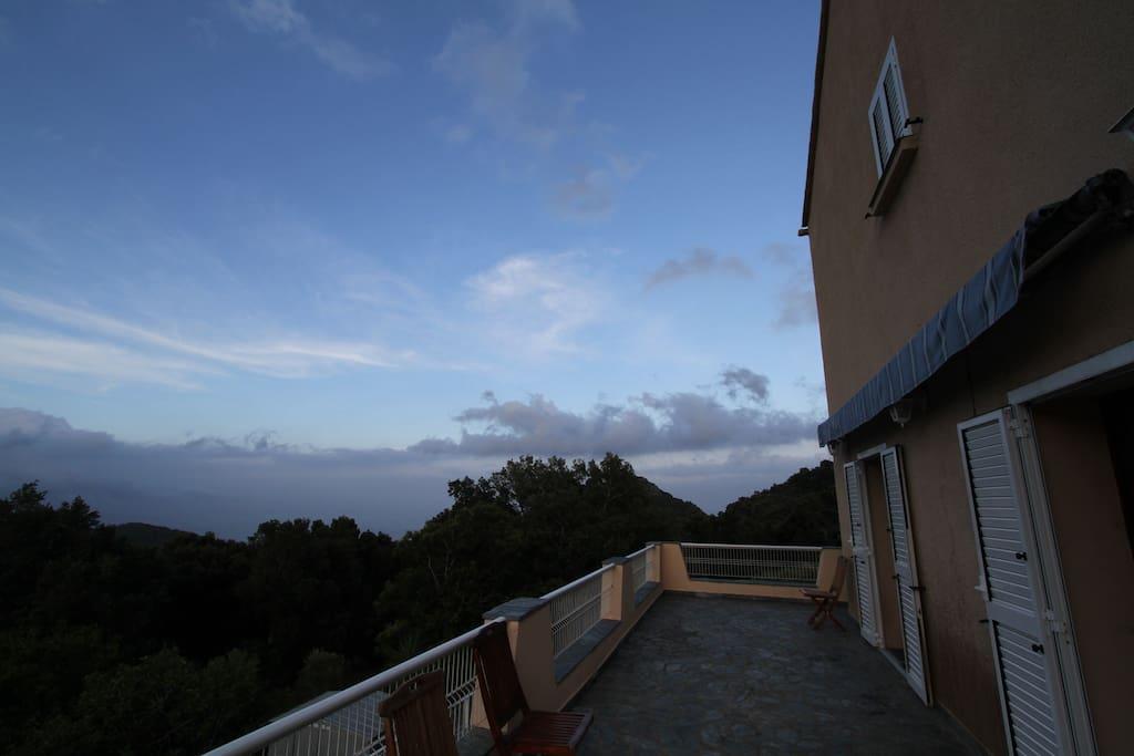Terrasse où le petit déjeuner sera servi, avec vue sur la vallée et la mer.