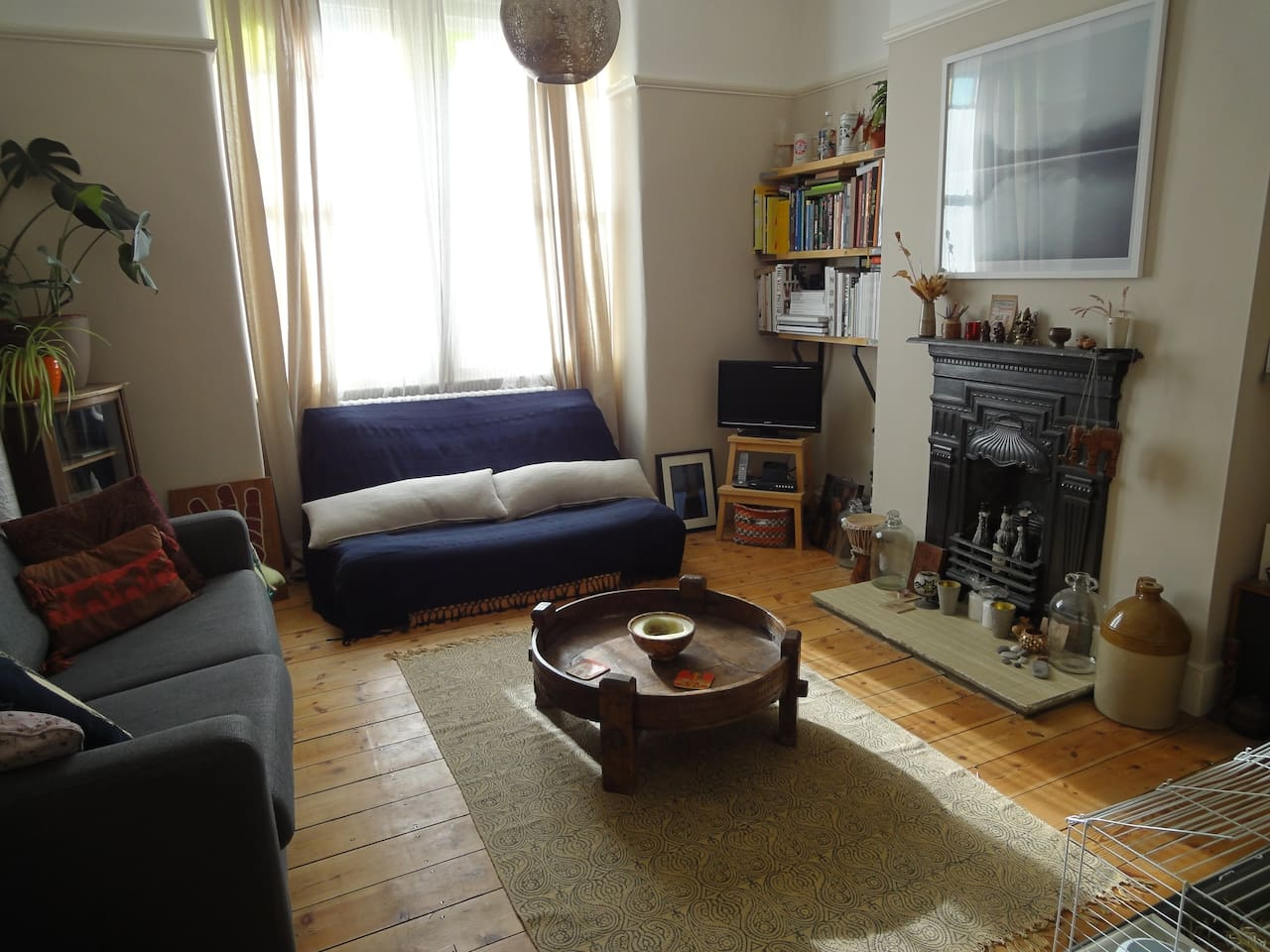 Our living room with period features including fireplace and original sash windows (with stained glass!). Lots of books for you to peruse.