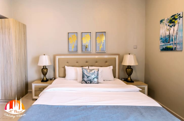The master bedroom offers a king sized bed, 2 bedsides, a wardrobe closet, en-suite bathroom and a private balcony with chairs.
