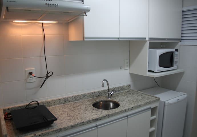 An equiped kitchen with micro wave, refrigerator an cook top