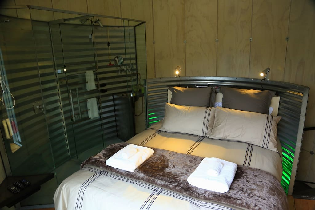 Queen bed and ensuite behind curved glass wall