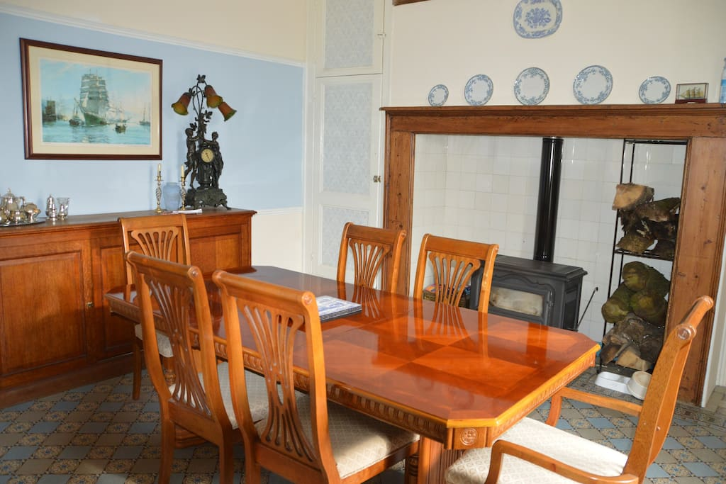 Family dining room with log burner and piano.