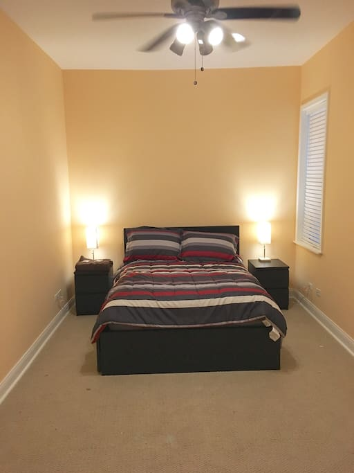 Main Master Bedroom with full size platform bed with built in drawers, walk-in closet in room, bedside tables lamps and remote controlled ceiling fan.