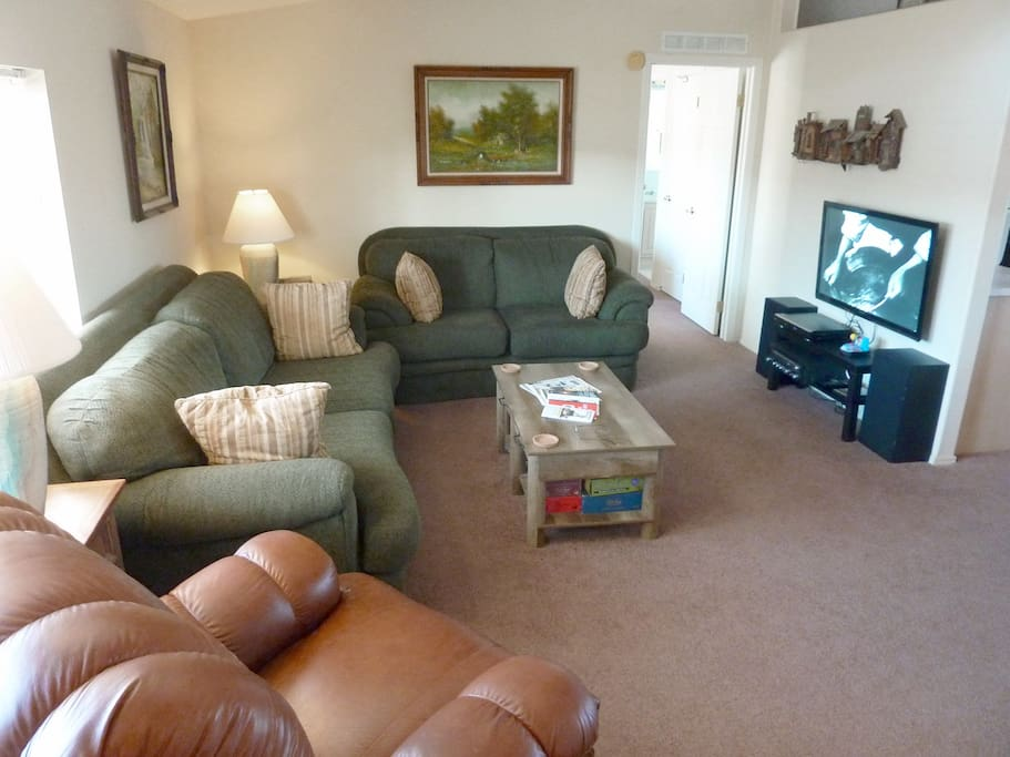 Living room with easy chair, couch, loveseat, TV, DVD player, kid's games, adult games