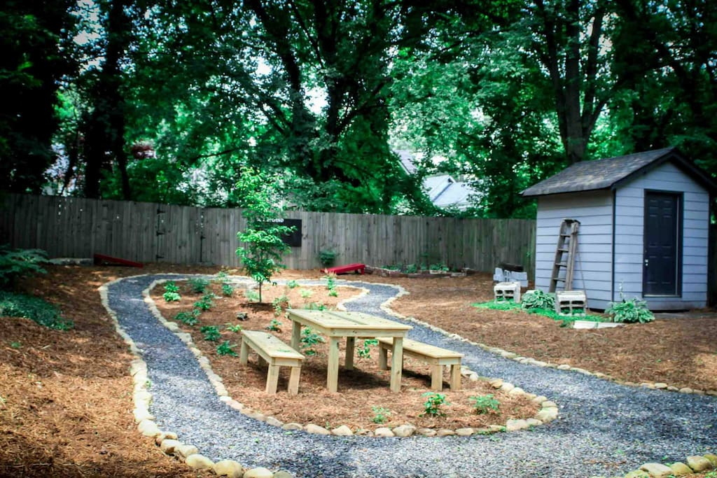 Back yard view with shed and cornhole boards out (herb garden with bench in back right corner and small firepit with stone in back left corner)