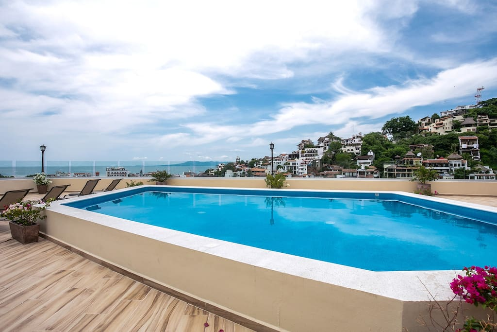 Sunny rooftop pool with views of the City and Banderas Bay