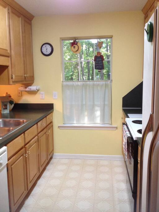Kitchen looks over woods and open to dining and living rooms. Fully stocked for cooking or just a cup of coffee!