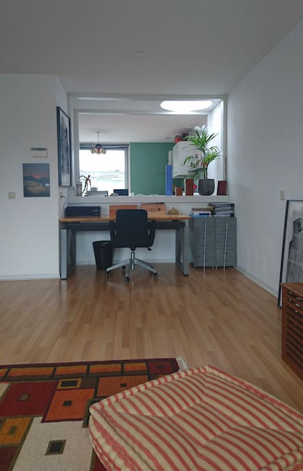 an open space between the living room and kitchen (and comfortable desk)