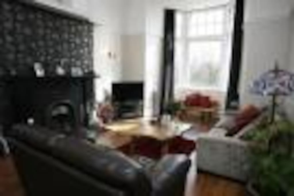 Lounge, with feature bay window with lovely views onto private gardens over the road. 15 feet high ceiling with ornate cornice work and feature marble fireplace.