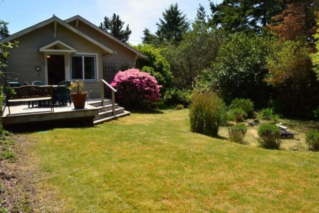 Large grassy landscaped backyard with firepit and deck with table, chairs and charcoal BBQ.