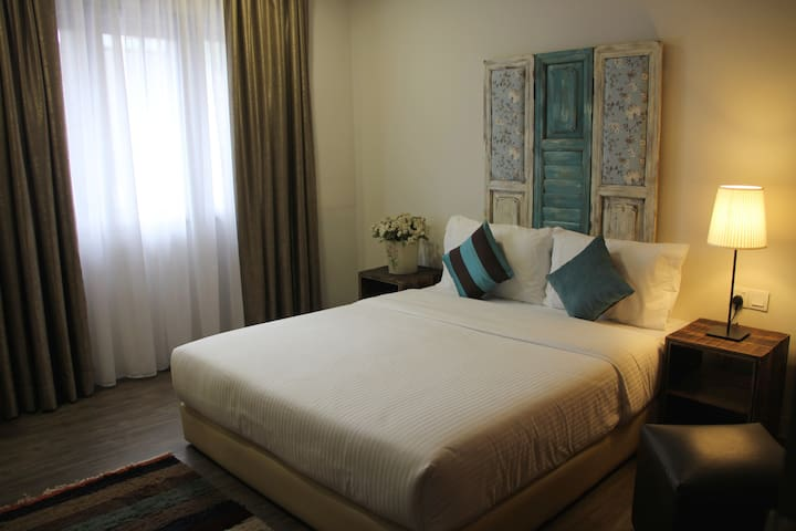 Deluxe room decorated with traditional wooden headboard and red bricks
