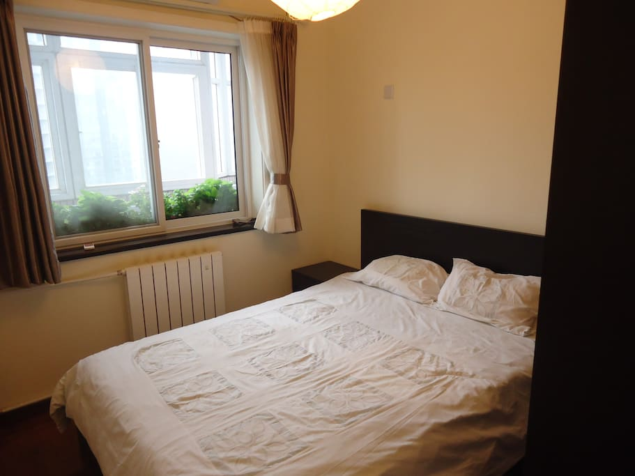 The guest room has a large wardrobe and plenty of storage under the bed. The window looks out onto a balcony decorated with lots of plants.