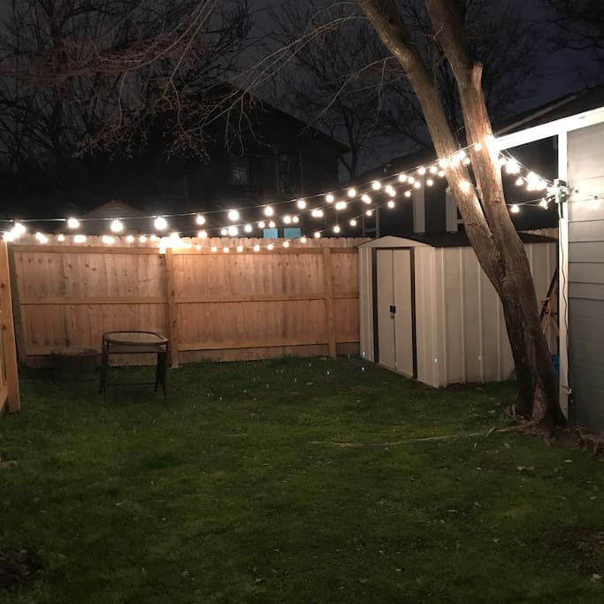 Back yard complete with stringed lights and small outdoor table