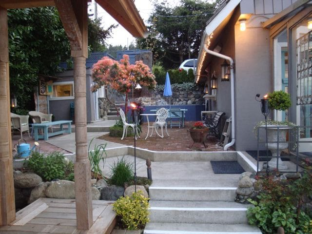 Patio with gas BBQ and dining tables leads to hot tub cabana and front door.