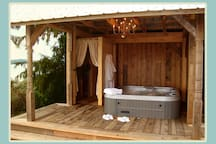 Hot tub cabana with change room, chandelier, and outdoor shower, overlooking the ocean and Coastal Mountain range.