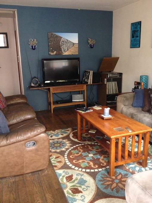 living room with tv and record player. large sectional couch optional for additional guests