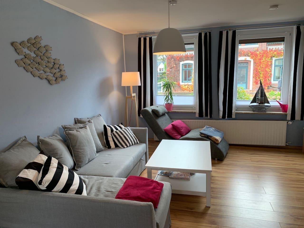 Gemütliches Wohnzimmer mit Schlafcouch und Kaminofen