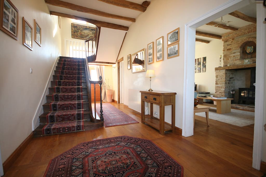 Hall with antique staircase and view into lounge